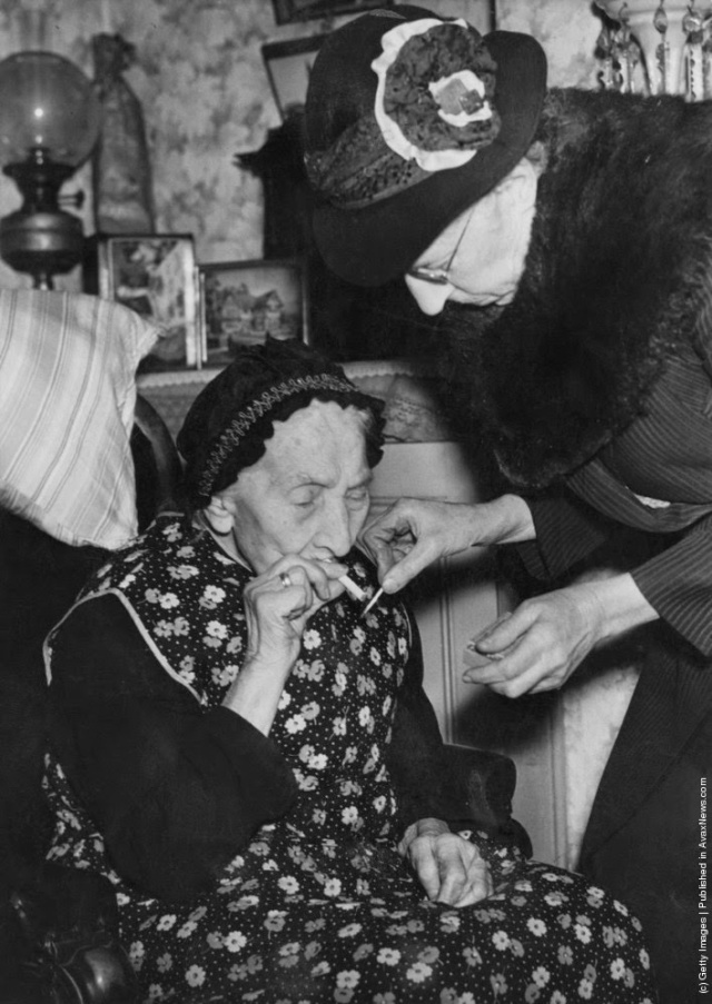 75 year-old Mary Parish lights a cigarette for her 101 year-old mother, Mary Ann Parish, at their home in Walworth, London, 14th February 1946. (Photo by Harry Todd/Fox Photos/Hulton Archive/Getty Images)