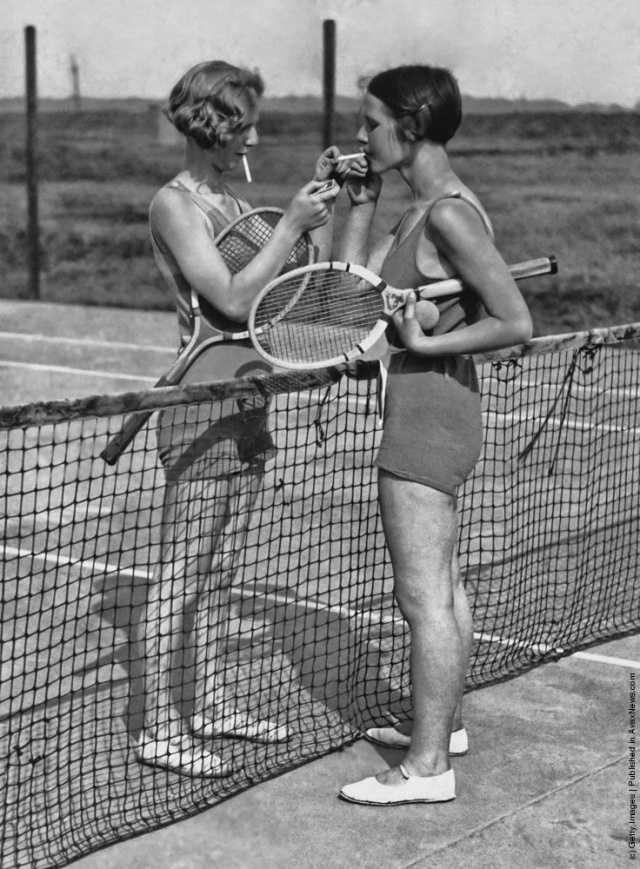 Two women lighting cigarettes on a tennis court in Essex, England circa 1930s. (Photo by Keystone View/FPG/Getty Images)